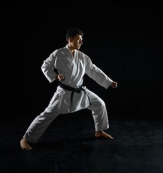 Боец-карате в боевой стойке. человек на тренировке карате, боевых искусствах, боевых соревнованиях