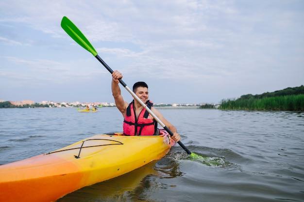 Male kayaker paddling kayak on lake