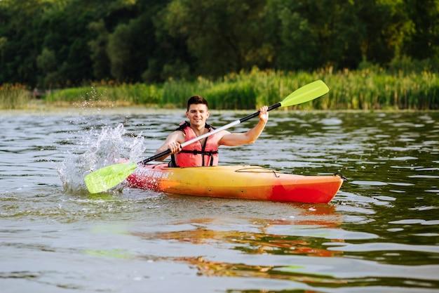 Male kayaker splashing water while kayaking on lake