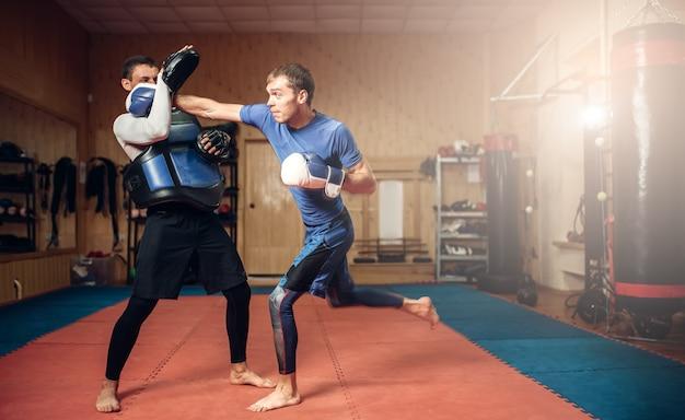 ハンドパンチを練習する手袋の男性キックボクサー