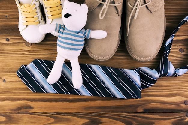 Male and kid boots near tie with soft toy