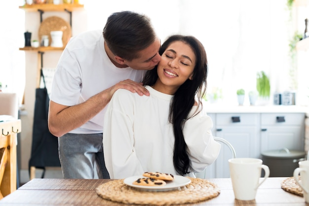 Male kissing on cheek ethnic young girlfriend