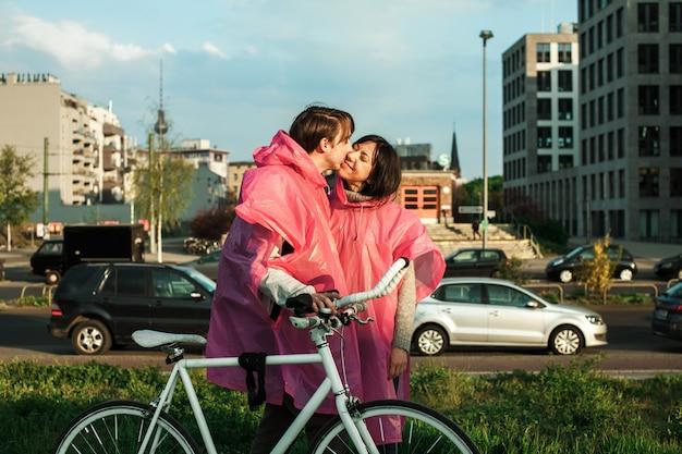 男性がデートで自転車で歩きながら彼のガールフレンドにキス
