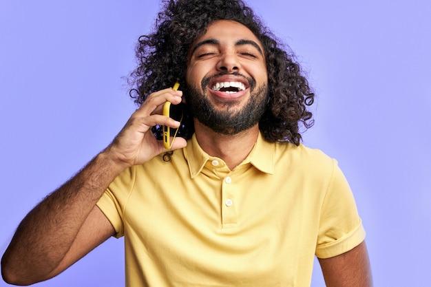 男性は友人と話をしながら電話で冗談を聞いて笑い、頭を投げ返す