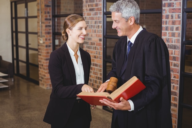 Male lawyer discussing over book with female colleague