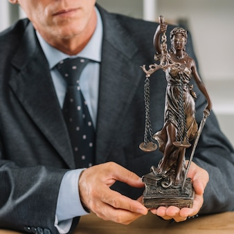 Male lawyer holding statue of justice in hand