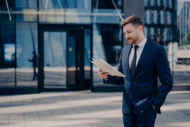 Мужчина-юрист в синем костюме читает газету, проверяет, есть ли что-нибудь важное, гуляя в одиночестве в офисе с рукой в кармане, молодой уверенный в себе бизнесмен наслаждается временем на свежем воздухе