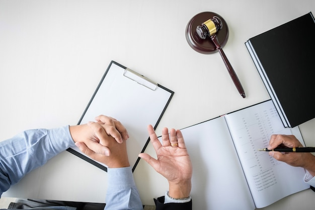 Male lawyer or judge consult with client and working with law books