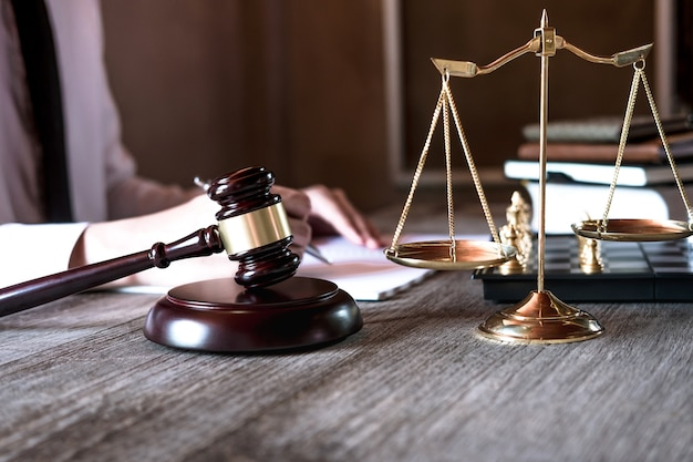 Male lawyer or judge working with law books, gavel and balance, report the case on table