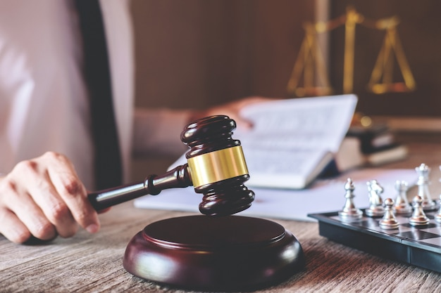 Male lawyer or judge working with law books, gavel and balance, report the case