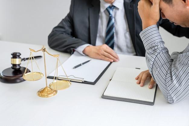 法廷で働く男性弁護士またはカウンセラーがクライアントと面会し、不動産、法律および法律サービスの概念に関する契約書と相談します。