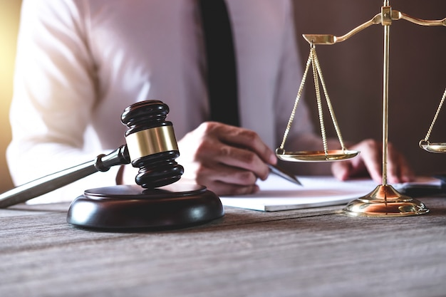 Мужской юрист или судья, работающий с юридическими книгами, молотком и балансом