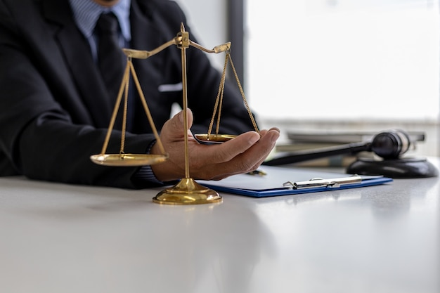 The male lawyer puts a second hand on the scales of justice on his desk, stating that the matter must be justified and not contrary to law and humanity. the concept of legal jurisprudence.