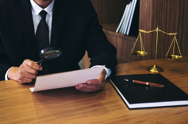 Male lawyer reading legal contract agreement and document