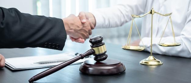 Мужчина-юрист пожимает руку клиенту после хорошей встречи по переговорам о сотрудничестве в зале суда.