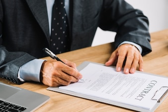 Male lawyer signing the contract with pen on clipboard