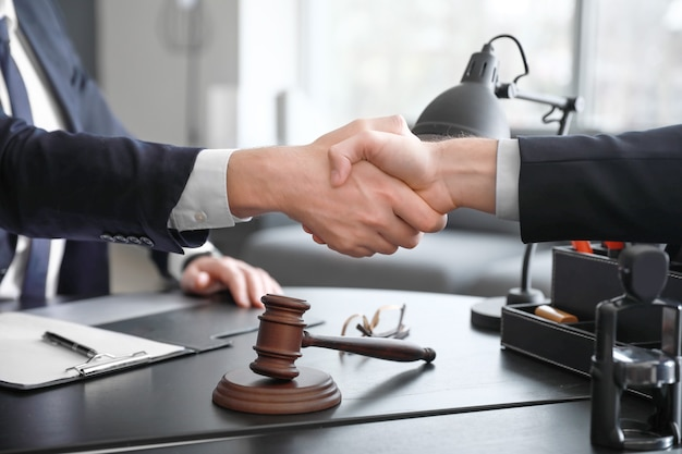 Male lawyer with client shaking hands in office