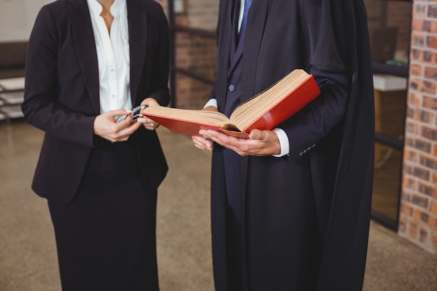 Male lawyer with female colleague discussing over book