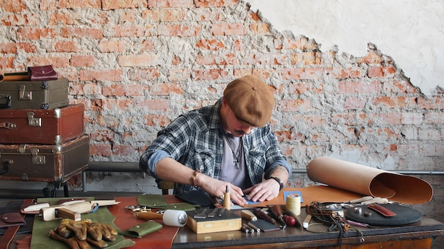 Male leather craftsman sews a leather wallet in the workshop. manufacture of handmade leather products.