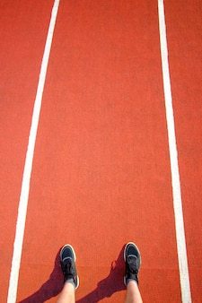 Male legs in black sneakers stay on red running track in stadium