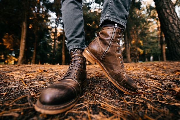 Male legs demonstrating brown leather stylish boots in autumn forest.