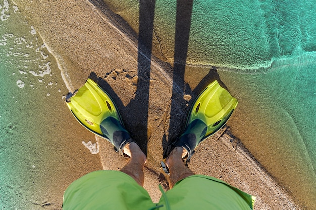 Male legs in flippers on a sandy beach by the sea. top view. diving training concept.