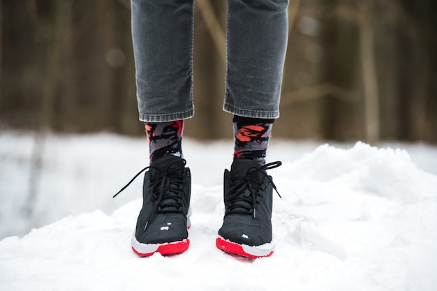 運動靴、トリミングされたジーンズ、雪の上に立っているファッショナブルな靴下の男性の足。