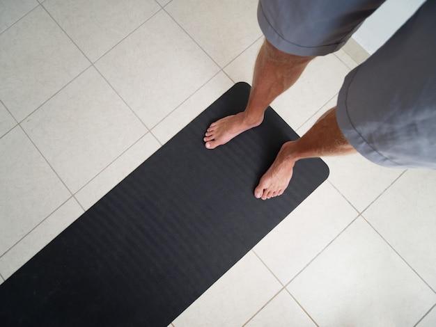 회색 반바지를 입은 남성 다리는 집에 있는 검은 요가 매트에 클로즈업되어 있습니다.