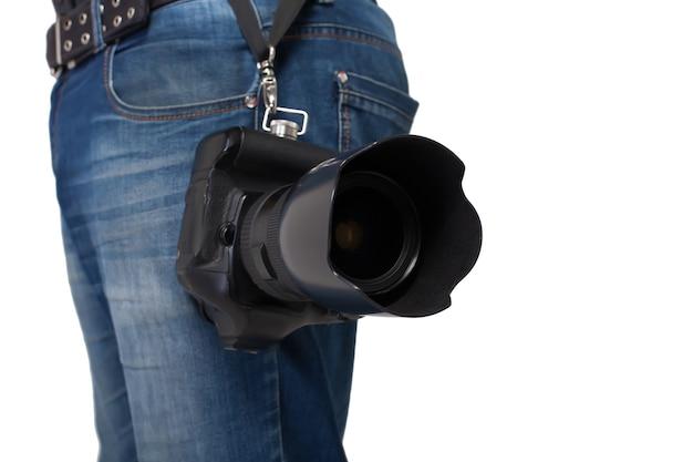 プロのレンズでデジタルカメラを保持しているジーンズとベルトの男性の足。写真ビジネスコンセプト