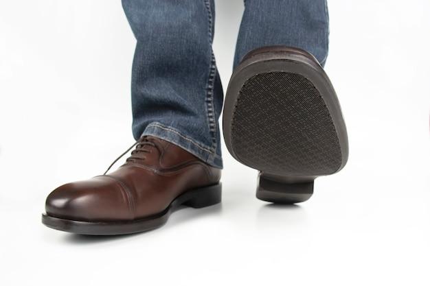 ジーンズの男性の脚と白い表面の茶色の古典的な靴