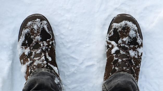 Мужские ноги в заснеженных зимних сапогах, вид сверху. зимняя прогулка по снегу. сосредоточьтесь на ногах. прекрасная белая зимняя погода со свежим снегопадом.