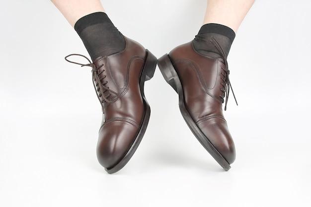 Мужские ножки в носках и коричневых классических туфлях на белом фоне