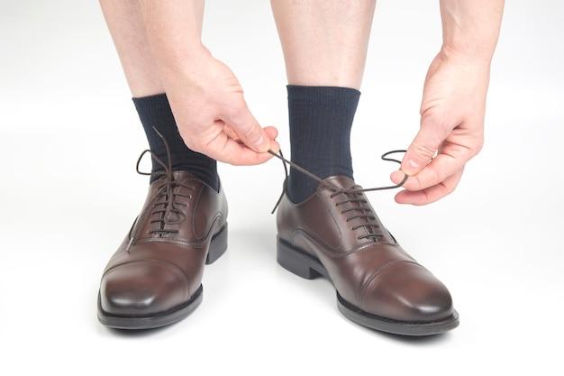 白い背景の上の靴下と茶色の古典的な靴の男性の脚