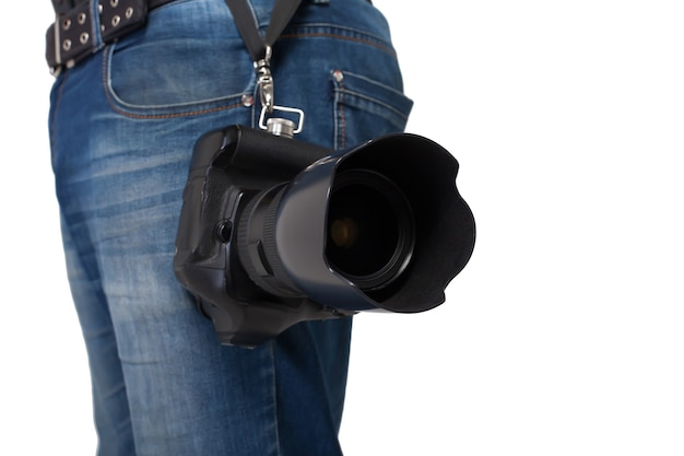 Male legs in jeans and belt holding digital camera with professional lens. photo business concept