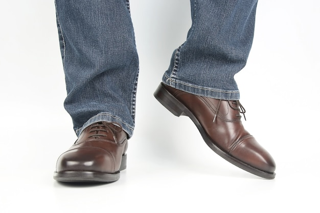 Male legs in jeans and brown classic shoes on white background