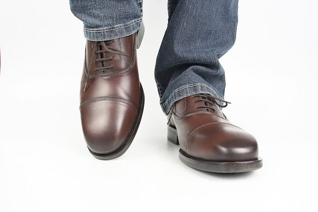 Male legs in jeans and brown classic shoes on white