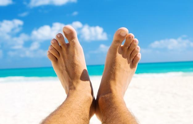 열 대 해변 배경 위에 남성 다리