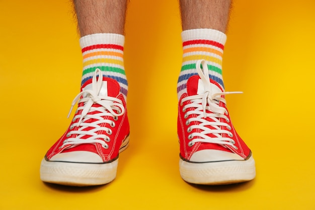 Male legs in red sneakers and lgbt socks