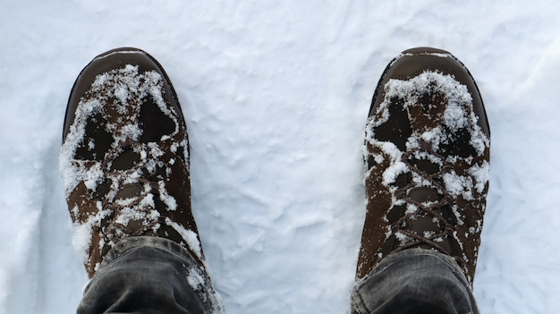 Male legs in snow-covered winter boots, top view. winter walk in the snow. focus on your legs. beautiful white winter weather with fresh snowfall.