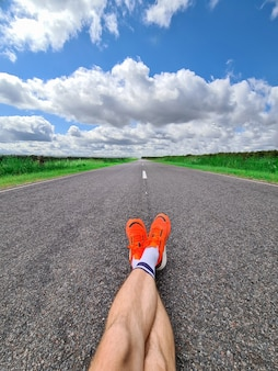 Male legs in sports sneakers lying on road against background of blue sky with clouds closeup