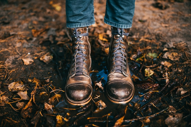 Male legs in stylish vintage boots standing on ground in autumn leaves