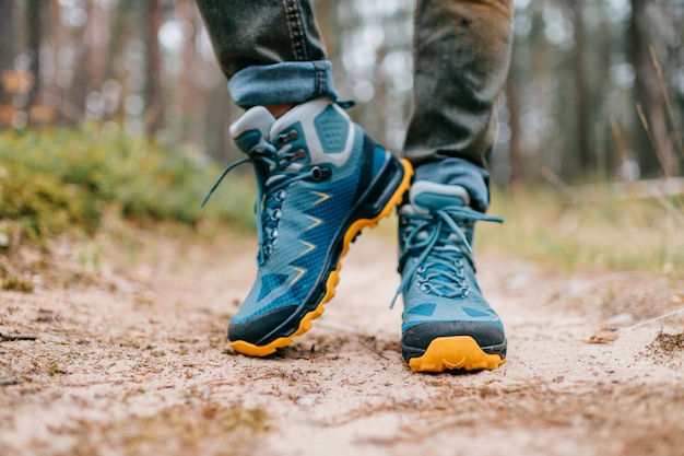 Male legs wearing sportive hiking shoes. mens legs in trekking boots for outdoor activity.