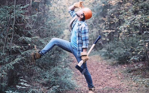 森の中のオスの木こり。プロのウッドカッターが木を伐採していないか検査します。