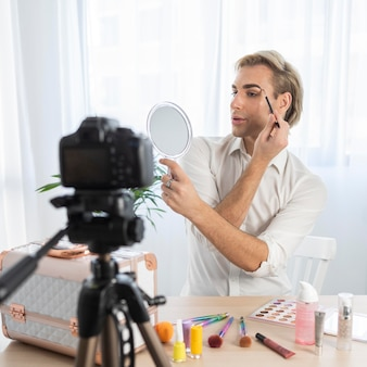 Male make-up look looking into the mirror