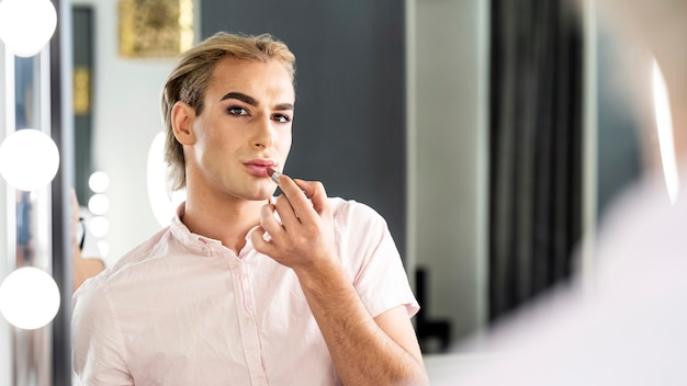 Male make-up look looking in the mirror