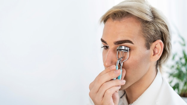 Male make-up look using an eyelash curler
