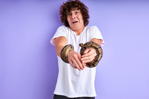 남성은 크롤링 손에 뱀을 잡고 재미있는 얼굴을 찡그린 다. 보라색 배경에 고립