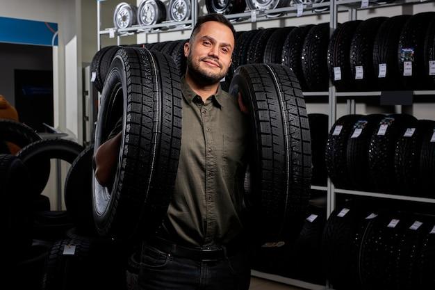 남성은 자동차 액세서리 상점에서 구매하고, 캐주얼웨어를 입은 쾌적하고 만족스러운 고객은 자동차 타이어를 들고 있습니다. 초상화
