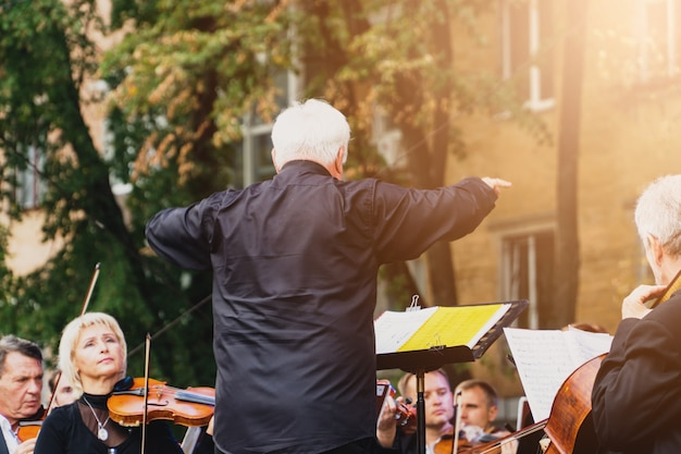 Male man conductor with his team on a festival outddors in sunny ukrainian poltava