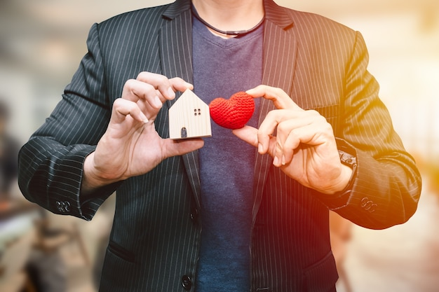 Male man hand holding small home and hart sign for love home or business accommodation service concept